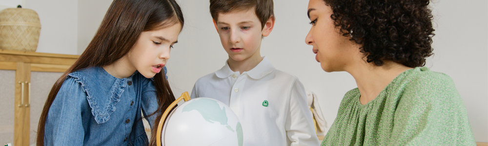 woman in green shirt shows two children a globe