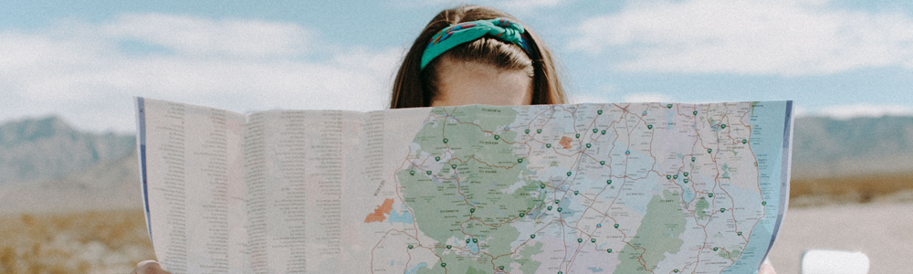 girl examines map with only the top of her head visible with mountains in the distance