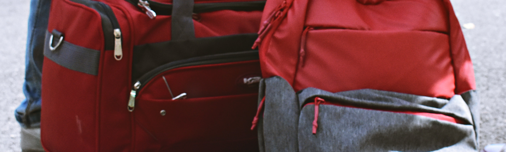 closeup of red backpack and red duffle bag