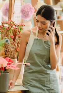 young woman takes an order at a floral shop