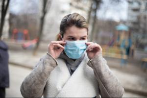 woman wearing winter coat adjusts face mask