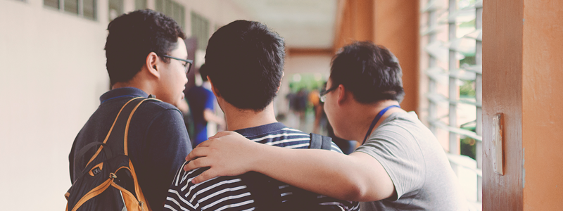 three male students with backpacks walk with arms around each others' shoulders