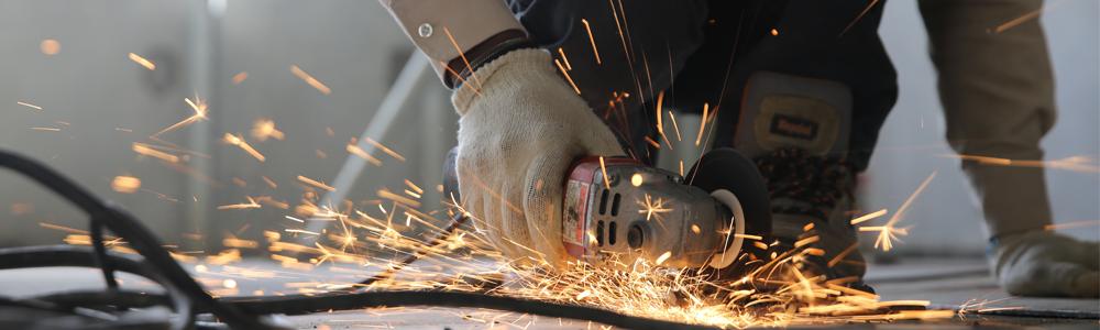 close up of hands using a grinder with sparks flying