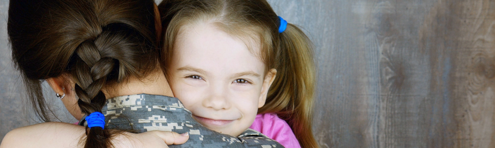 girl in pink shirt hugs mother in military fatigues