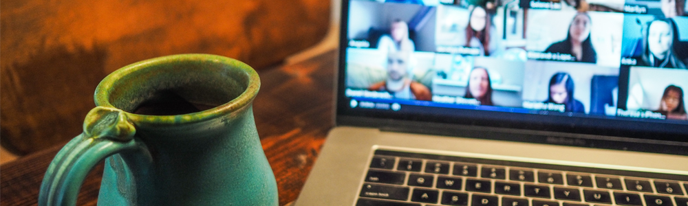 close up of coffee cup and computer monitor with video conference call