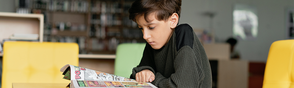 child reads graphic novel in classroom