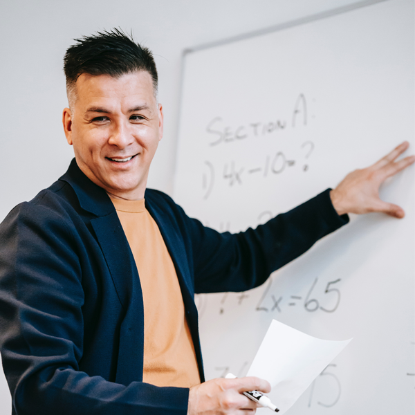teacher addresses classroom from whiteboard