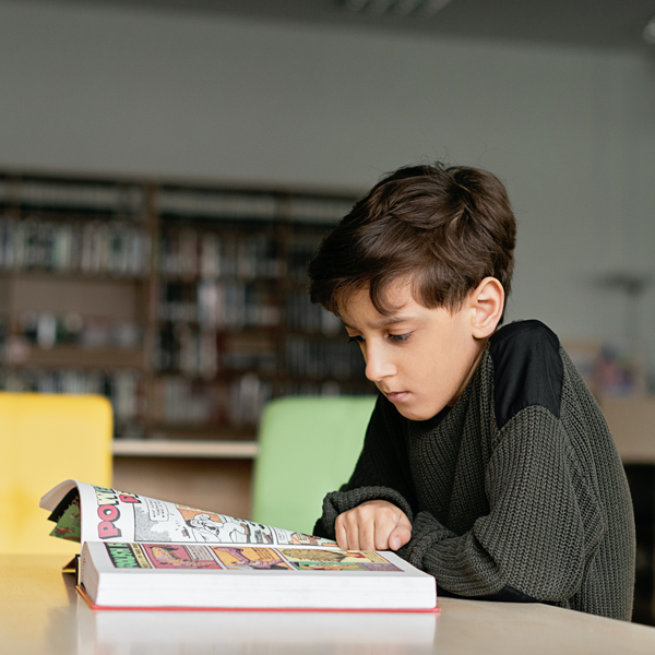 young boy reads graphic novel in library
