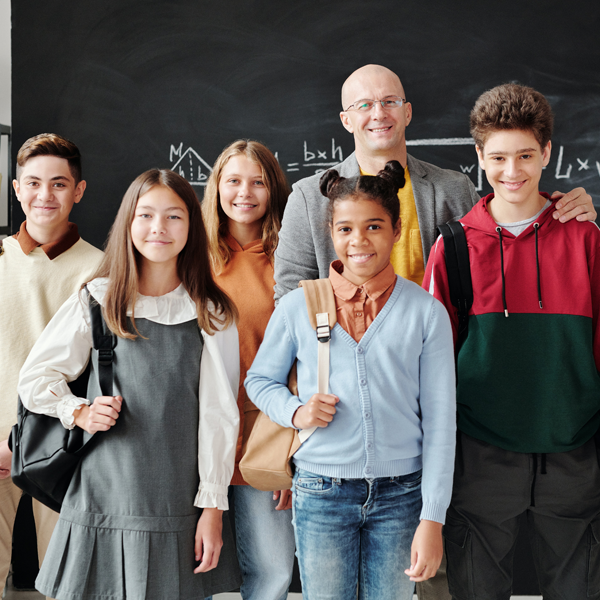teacher stands with group of middle school students