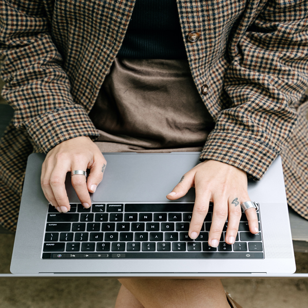 woman in plaid coat uses laptop