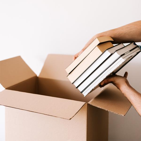 closeup of hands loading books into cardboard box