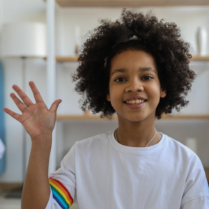 young girl in white tee shirt smiles and waves at camera