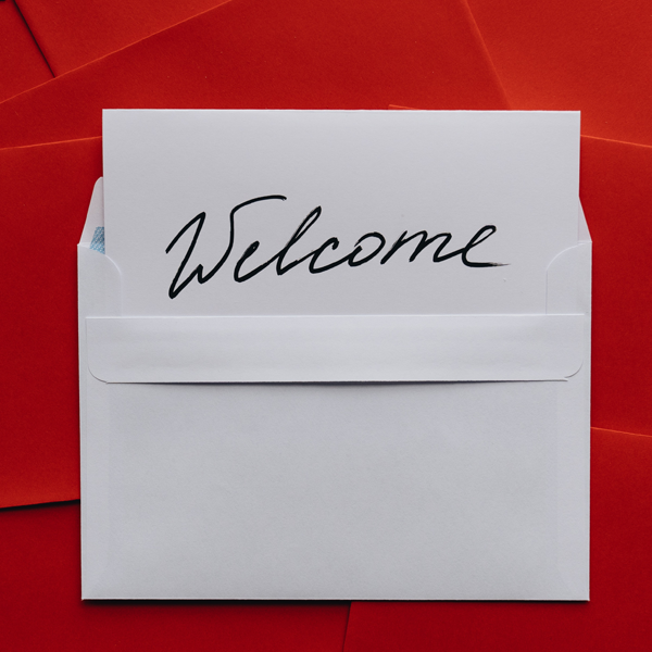 welcome on notecard in white envelope on red background