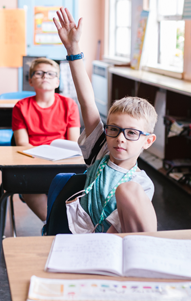 student in blue tee shirt and glasses raises hand in classroom